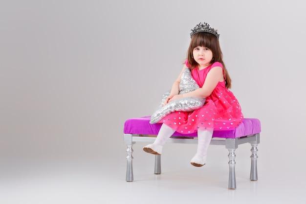 Schönes kleines brünettes mädchen im rosa prinzessinkleid mit krone, die auf einem rosa stuhl sitzt und mit kissen spielt. süßes baby