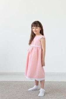 Schönes kleines brünettes mädchen in einem rosa kleid, das auf einer weißen oberfläche aufwirft