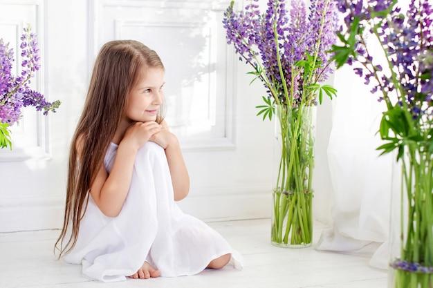 Schönes kleines emotionales mädchen, das unter violetten blumen sitzt. ein blumendekor in einem innenraum