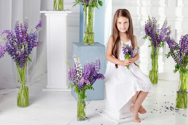 Schönes kleines emotionales mädchen sitzt unter violetten blumen. ein blumendekor in einem innenraum