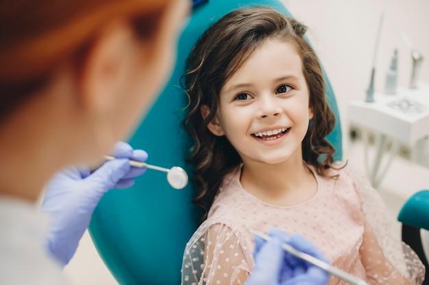 Schönes kleines kind, das lächelt, während es mit dem kinderzahnarzt spricht, nachdem es eine zehnte untersuchung in einer kinderstomatologie durchgeführt hat.