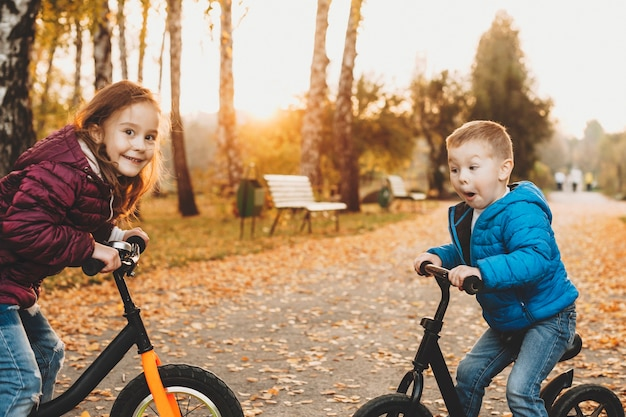 Schönes kleines kind, das spaß mit seiner schwester hat, während sie auf ihren fahrrädern otudor im park von angesicht zu angesicht sitzen.
