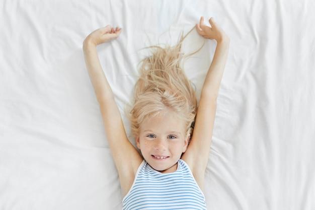 Schönes kleines kind mit blauen augen und sommersprossen, die sich morgens im bett ausdehnen, freudig aussehen, entspannung genießen und einen neuen tag beginnen wollen.