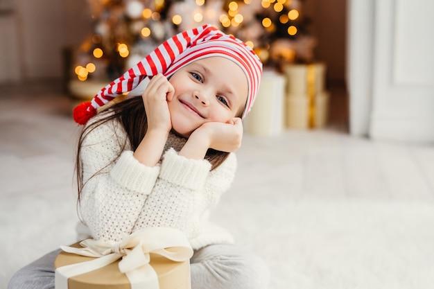 Schönes kleines kind wirft im wohnzimmer auf, lehnt sich am gegenwärtigen geschenk, hat glücklichen ausdruck, freut sich, überraschung von den eltern zu erhalten, verbringt feiertage im familienkreis. frohe weihnachten und ein glückliches neues jahr