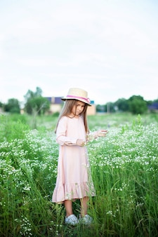 Schönes kleines lächelndes mädchen im rosa kleid und im strohhut im feld der gänseblümchen. kind im feld der blühenden kamille im sommer.