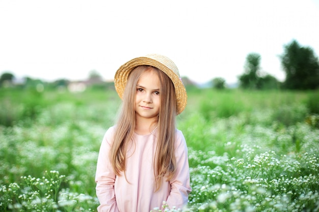 Schönes kleines lächelndes mädchen im rosa kleid und im strohhut im feld der gänseblümchen. nettes kind im feld der blühenden kamille im sommer.
