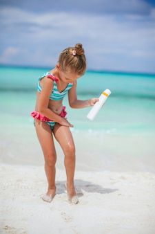 Schönes kleines mädchen am strand mit sonnencremeflasche. sonnenschutz