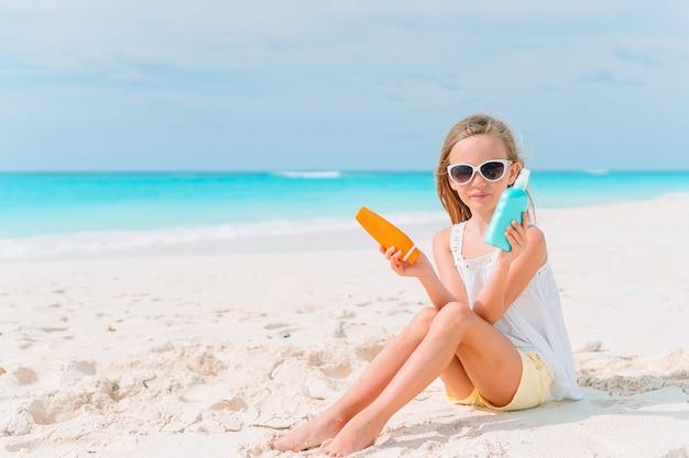 Schönes kleines mädchen am strand mit sonnencremeflasche