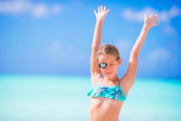 Schönes kleines mädchen am strand spaß haben. glückliches mädchen genießen sommerferienhintergrund den blauen himmel und das türkiswasser im meer auf karibischer insel