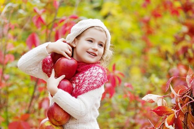 Schönes kleines mädchen, das äpfel im herbstgarten hält. . kleines mädchen, das im apfelbaumobstgarten spielt. kleinkind, das früchte an der fallernte isst. outdoor-spaß für kinder. gesunde ernährung