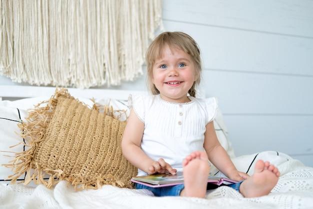 Schönes kleines mädchen, das auf dem bett sitzt und ein buch liest