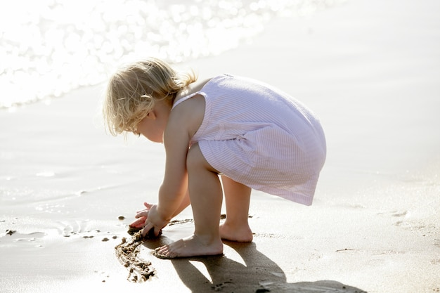 Schönes kleines mädchen, das auf dem strand spielt