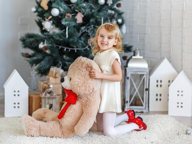 Schönes kleines mädchen, das auf ein wunder in der weihnachtsdekoration wartet