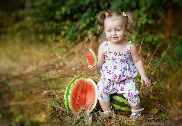 Schönes kleines mädchen, das auf einer wassermelone sitzt. lebensstil und gesunde ernährung.