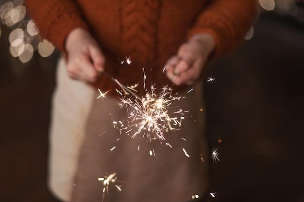 Schönes kleines mädchen, das brennende bengalische lichter in den händen hält