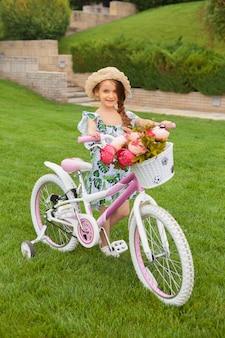 Schönes kleines mädchen, das ein fahrrad durch den park reitet. natur, lebensstil