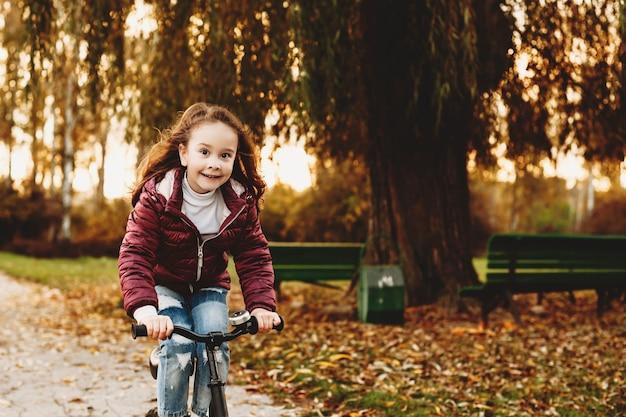 Schönes kleines mädchen, das ein fahrrad im park gegen sonnenuntergang reitet, während kamera lächelnd betrachtet.
