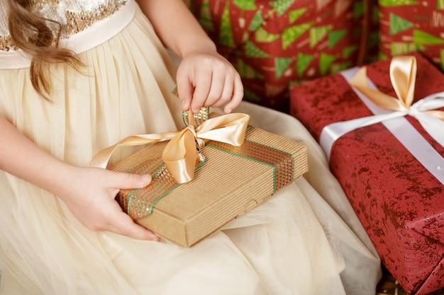 Schönes kleines mädchen, das eine weihnachtsgeschenkbox öffnet. weihnachts- und neujahrsfeier.
