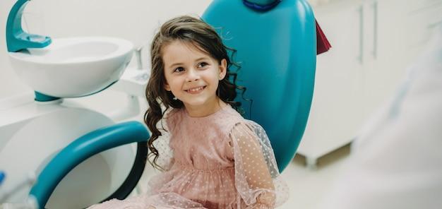 Schönes kleines mädchen, das ihren kinderstomatologen lächelnd vor der zahnuntersuchung in der kinderzahnheilkunde betrachtet.