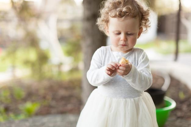 Schönes kleines mädchen, das ihren snack in der straße betrachtet