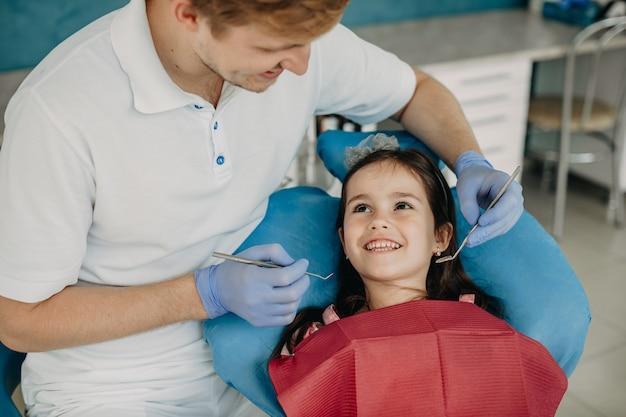 Schönes kleines mädchen, das im stomatologischen stuhl sitzt und ihren lächelnden zahnarzt vor einer zahnoperation betrachtet