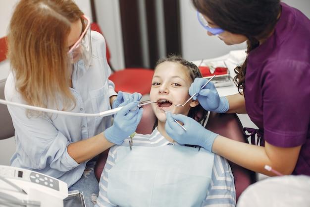 Schönes kleines mädchen, das in der zahnarztpraxis sitzt