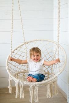 Schönes kleines mädchen, das in einem hängenden stuhl schwingt