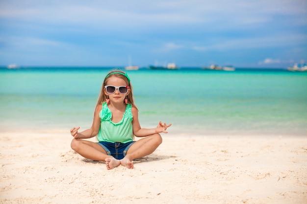 Schönes kleines mädchen, das in einem lotussitz auf einem exotischen strand sitzt