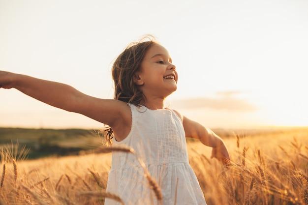 Schönes kleines mädchen, das mit hand oben in einem weizenfeld gegen sonnenuntergang lacht und läuft. freiheitskonzept.