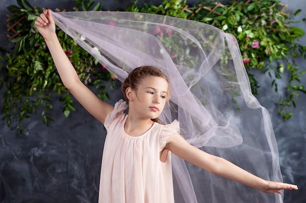 Schönes kleines mädchen, das mit leichtem stoff gegen die blumen spielt. porträt des netten kleinen mädchens. kleines mädchen tanzen.