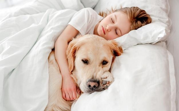 Schönes kleines mädchen, das morgens mit golden retriever hund im bett bleibt, ihn umarmt und ein nickerchen macht. kind, das zu hause mit haustier schläft. porträt der freundschaft zwischen mensch und tier