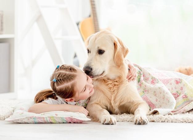 Schönes kleines mädchen, das niedlichen hund mit decke auf boden im spielzimmer bedeckt