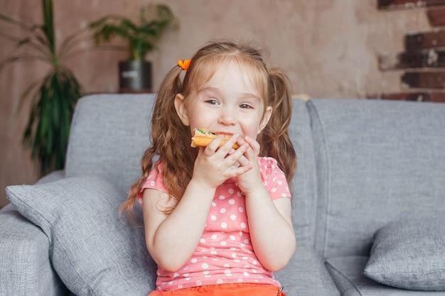 Schönes kleines mädchen, das pizza zu hause isst