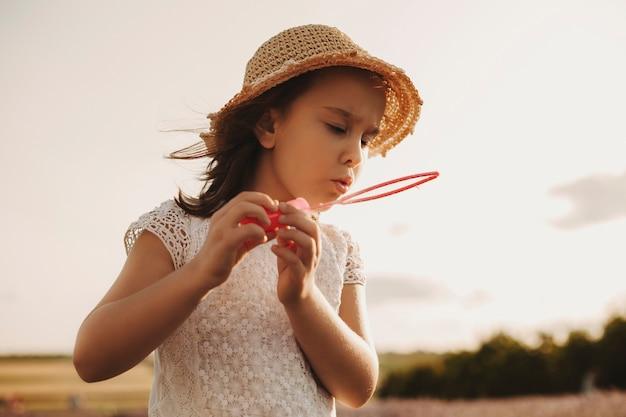 Schönes kleines mädchen, das seifenblasen draußen auf dem spielplatz bläst. süßes kind, das mit blasen außerhalb gegen sonnenuntergang spielt.