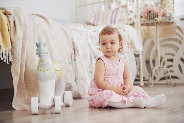 Schönes kleines mädchen, das spielwaren spielt. blauäugige blondine. weißer stuhl. kinderzimmer. glückliches kleines mädchenporträt. kindheitskonzept
