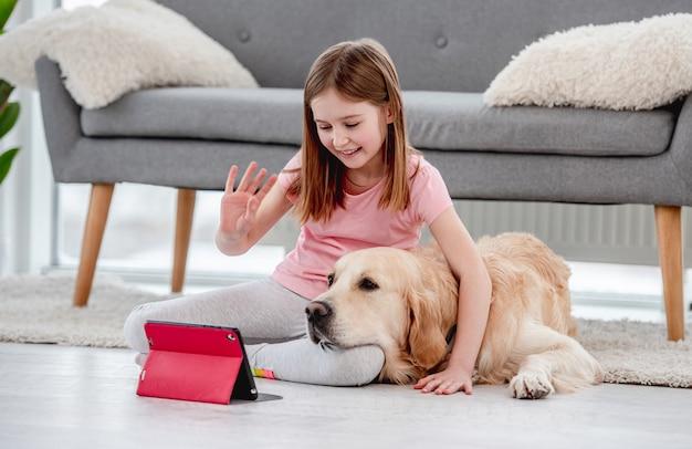 Schönes kleines mädchen, das während der online-kommunikation mit freunden auf dem tablet mit golden retriever hund auf dem boden sitzt