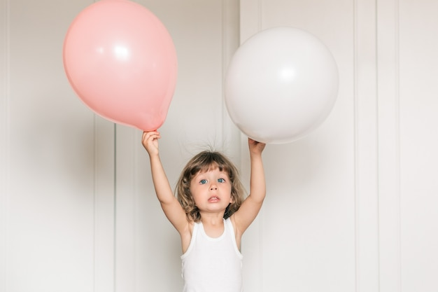 Schönes kleines mädchen feiert geburtstag mit ballon. minimalistischer weißer hintergrund. glücklicher lebensstil