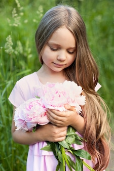 Schönes kleines mädchen hält eine rosa pfingstrose an einem sonnigen tag im garten.