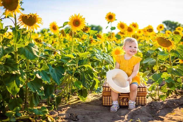 Schönes kleines mädchen im blühenden sonnenblumenfeld im sommer
