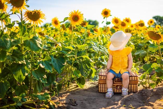 Schönes kleines mädchen im blühenden sonnenblumenfeld im sommer Premium Fotos