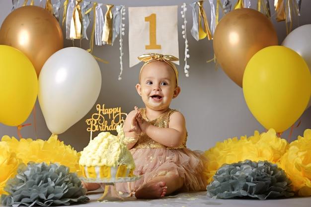 Schönes kleines mädchen im gelben kleid mit süßem kuchen