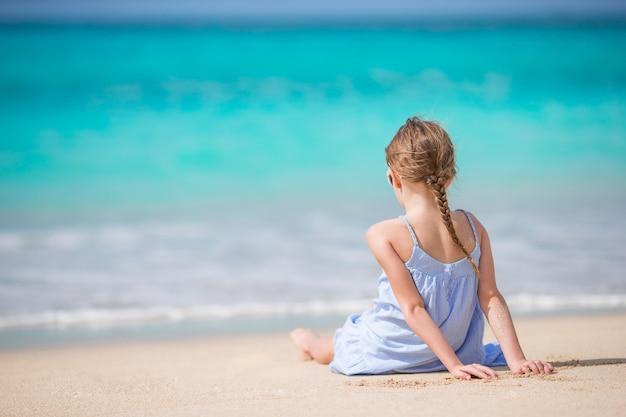 Schönes kleines mädchen im kleid am strand, der spaß hat.