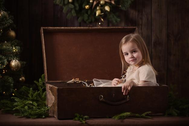 Schönes kleines mädchen im kleid mit weihnachtsbaum im retro-stil