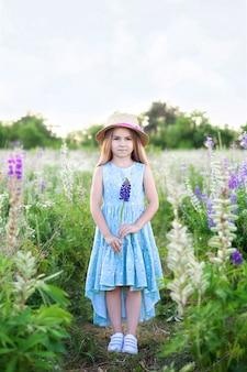 Schönes kleines mädchen im kleid und im strohhut hält lupinenblume bei sonnenuntergang in einem blühenden feld. kinder spielen im freien.