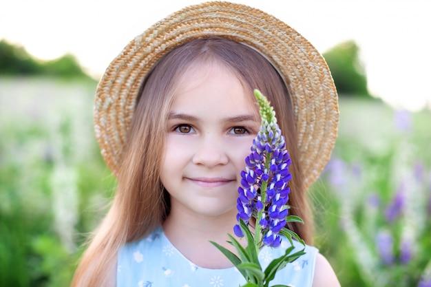 Schönes kleines mädchen im strohhut hält eine lupinenblume bei sonnenuntergang im blühenden feld. naturbegriff. glückliche kindheit. nahaufnahmeporträt des gesichtes eines niedlichen kleinen mädchens. sommerferien und ferien