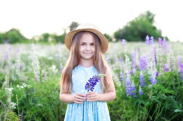 Schönes kleines mädchen im strohhut hält eine lupinenblume bei sonnenuntergang im blühenden feld. naturbegriff. glückliche kindheit. nahaufnahmeporträt des niedlichen kleinen mädchens. sommerferien und ferien. kinderspiel