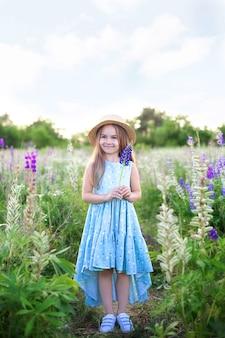 Schönes kleines mädchen im strohhut hält eine lupinenblume bei sonnenuntergang im blühenden feld. naturbegriff. glückliche kindheit.
