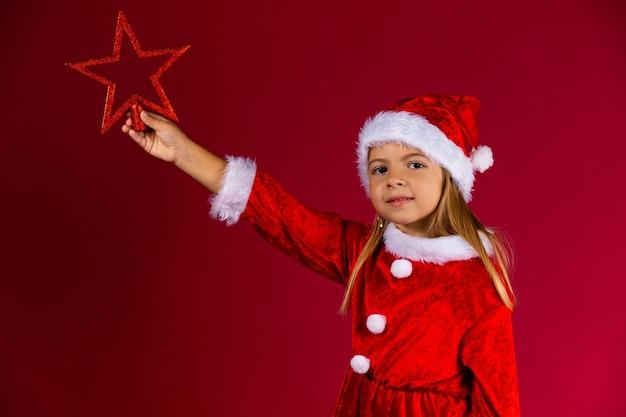 Schönes kleines mädchen im weihnachtsmannkleid und -hut hält roten weihnachtsstern, lokalisiert auf roter wand