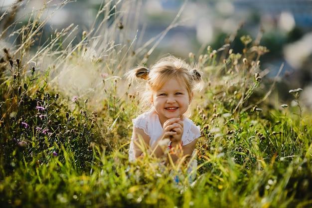 Schönes kleines mädchen im weißen hemd und in den jeans sitzt auf dem rasen mit großer landschaft