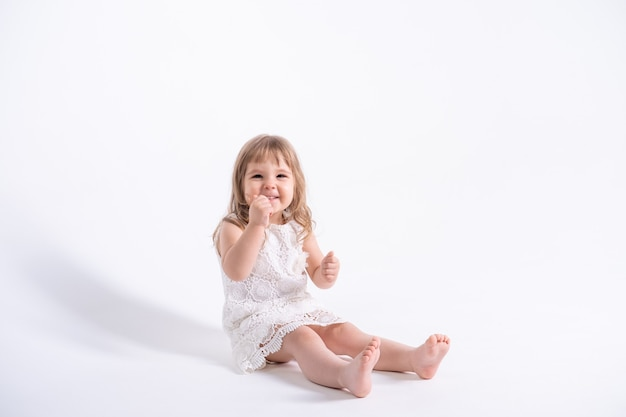 Schönes kleines mädchen im weißen kleid, das auf weißer wand sitzt.